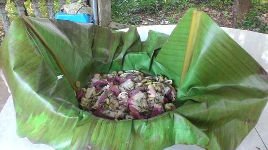 Sau khi ướp xong, thịt được gói vào lá chuối đã hơ nóng cho mềm