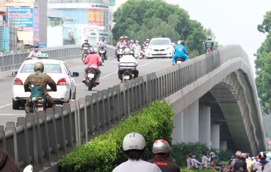 Điểm cao nhất của thành cầu ngang với hông người đi xe máy