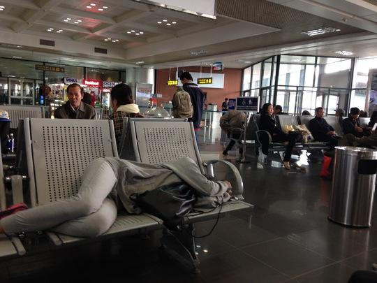 Một hành khách nằm chờ ra máy bay tại sân bay Nội Bài. Ảnh: T.Phương