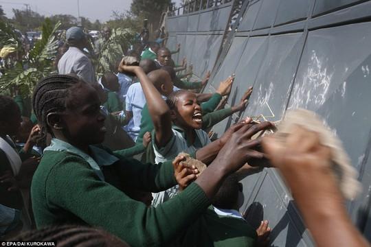 Các học sinh phá hàng rào chặn lối vào sân chơi. Ảnh: EPA