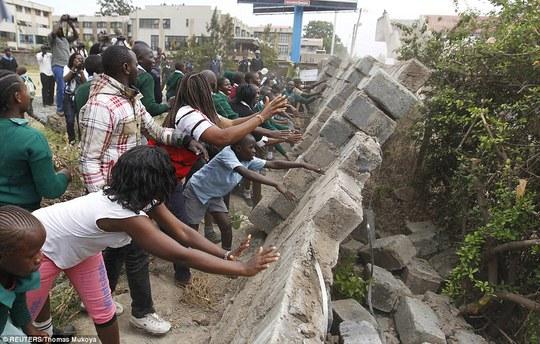 Học sinh phá vỡ bức tường xung quanh sân chơi. Ảnh: Reuters