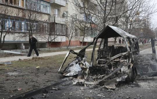 Một chiếc xe cháy rụi sau khi trúng pháo kích ở Mariupol hôm 24-1. Ảnh: Reuters