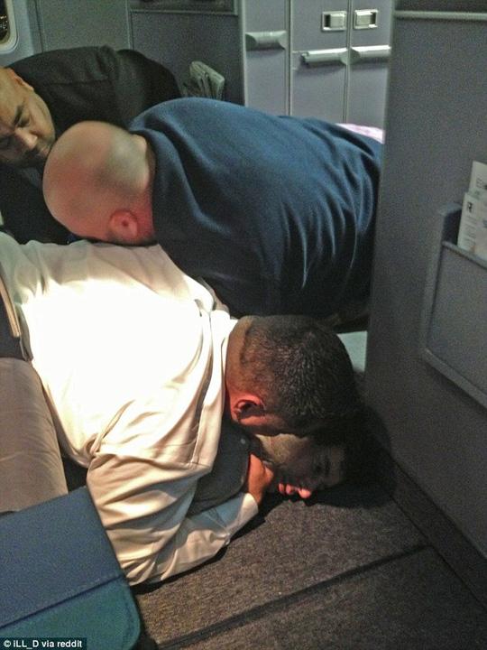 Các hành khách ngăn người đàn ông gây rối trên máy bay. Ảnh: Daily Mail