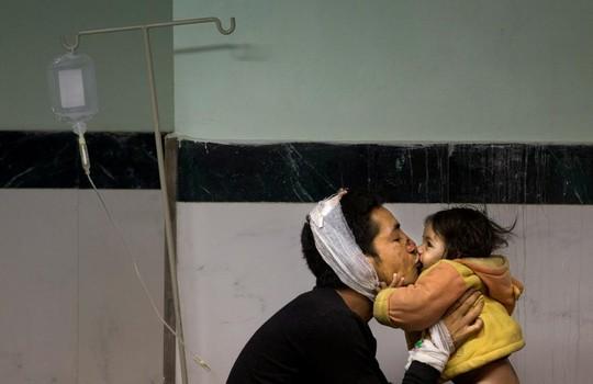 Một người cha tên Suresh Parihar bên cô con gái Sandhya trong bệnh viện. Ảnh: AP