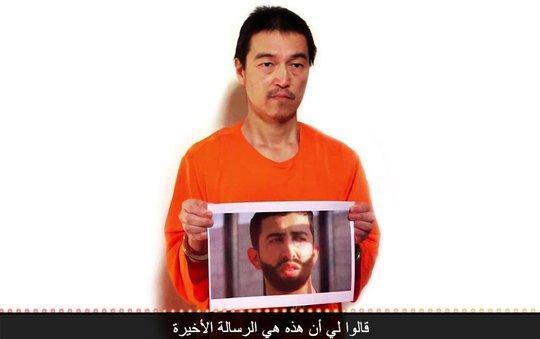 Hình ảnh nhà báo Goto cầm ảnh chân dung phi công người Jordan trong đoạn video mới công bố. Ảnh: NY Times