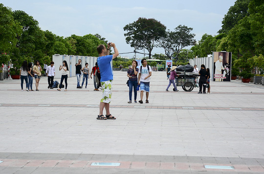 Người dân và du khách nước ngoài đang dạo chơi thì một người phụ nữ đẩy xe ve chai băng ngang như chốn không người