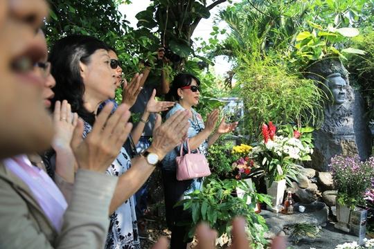 Ca sĩ Trịnh Vĩnh Trinh (người phụ nữ đeo kính râm), em ruột Trịnh Công Sơn, hát cùng người đến viếng mộ