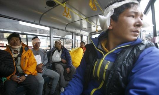 Các hướng dẫn viên du lịch ở Everest đang được chuyển bằng xe buýt đến nơi an toàn. Ảnh: AP
