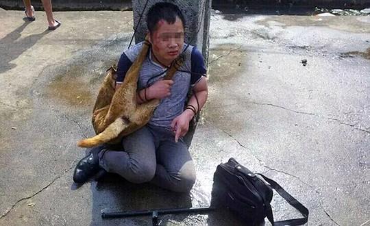 Người dân buộc xác chó lên cổ một trong hai người đàn ông. Ảnh: Daily Mail