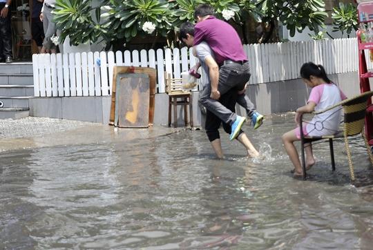 Hai thanh niên cõng nhau qua dòng nước ngập