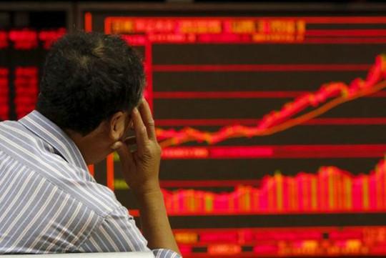Một nhà đầu tư trầm ngâm theo dõi thông tin chứng khoán ở Bắc Kinh hôm 9-7. Ảnh: Reuters