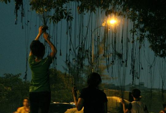 Chiều và đêm xuống, người bán quần áo lề đường dùng gậy kéo chùm dây trên cây xuống để mắc quần áo