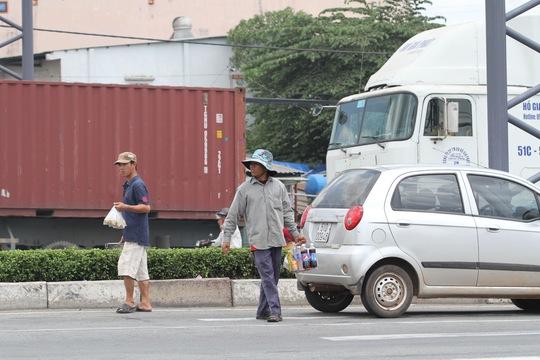 Giữa dòng xe container, xe tải, những người này cố gắng luồn lách để bán từng chai nước, bịch đậu phộng