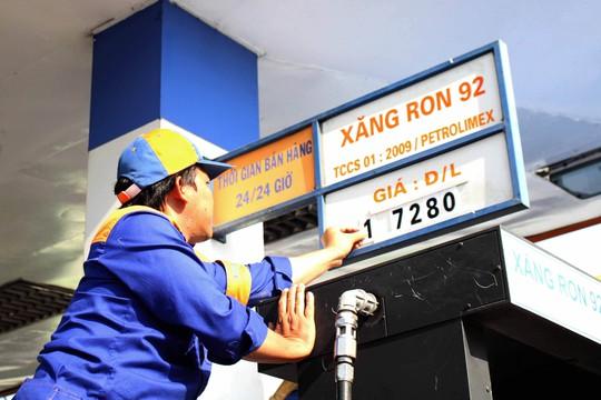 Nhân viên một cây xăng tại TP HCM đang niêm yết giá bán mới vào chiều 11-3 Ảnh: HOÀNG TRIỀU