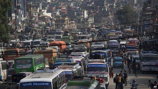 Dòng xe buýt đông nghẹt rời khỏi Kathmandu. Ảnh: AP