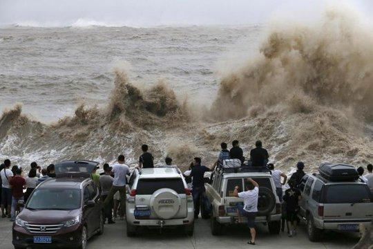 Người Trung Quốc xem cảnh sóng dâng cao do bão đổ bộ. Ảnh: Reuters