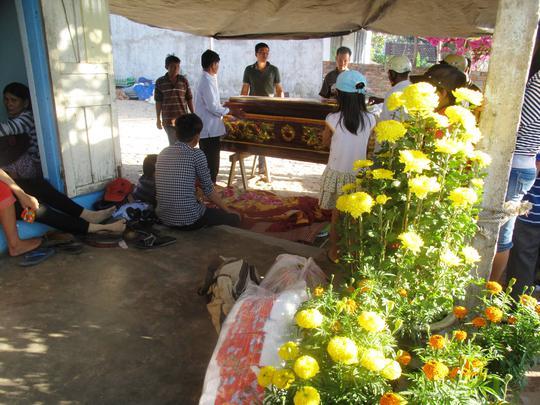 Quan tài để đưa Nguyễn Đông Hải về nơi an nghỉ được đặt cạnh những chậu hoa chưa kịp chưng tết