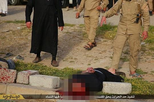 Một chiến binh IS khác bồi thêm một tảng để chắc chắn người đàn ông không ngóc đầu dậy được. Thủ cấp của họ bị nát bấy, máu chảy lênh láng. Ảnh: Daily Mail