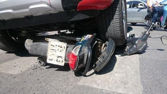 Đầu xe máy bị bánh xe ô tô đè lên