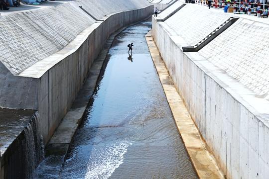 Một phóng viên lội giữa dòng kênh vì cho rằng nước kênh không bẩn và độc như trước