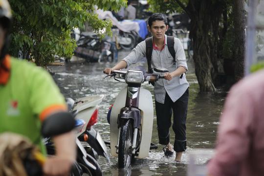 Một thanh niên đang chán nản vì xe chết máy phải dắt bộ trong đoạn đường nước ngập sâu