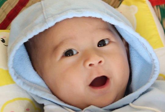 Khuôn mặt hồn nhiên tươi cười của bé Quốc Huy