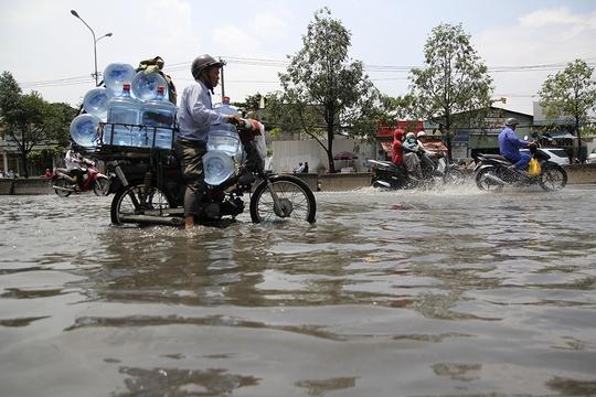 Một người đàn ông loay hoay giữa dòng nước, khi trên xe chở hàng cồng kềnh.