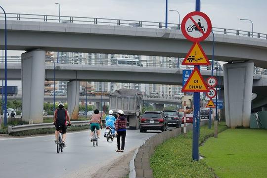 Không chỉ xe máy mà nhiều phương tiện xe đạp và đi bộ cũng lưu thông trên cầu vượt, bất chấp nguy hiểm
