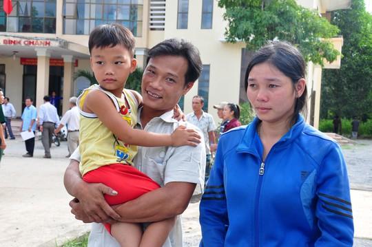 Ngư dân Nguyễn Phú Cầu ôm chặt đứa con trai 5 tuổi vào lòng. Ảnh: Tử Trực