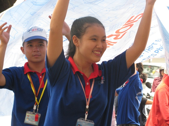Một sinh viên tình nguyện căng vải bạt che mưa cho thí sinh