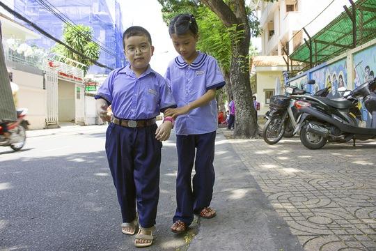 Huỳnh Giao dắt tay một người bạn khuyết tật sau giờ tan học