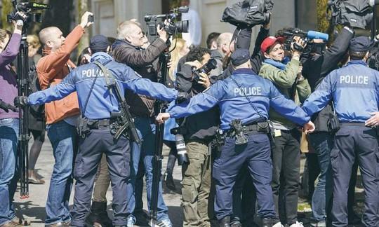 Kiên nhẫn lấy tin trước vòng phong tỏa của cảnh sát. Ảnh: Reuters