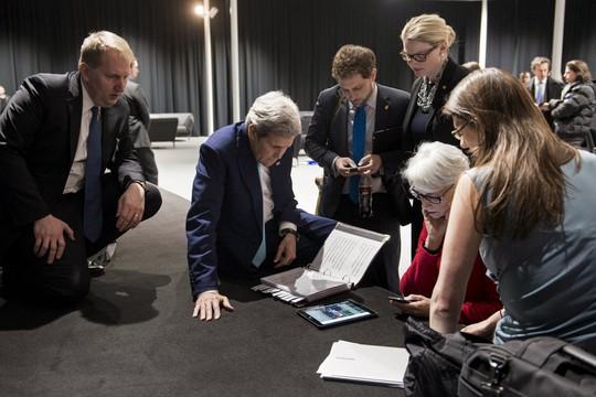 Ngoại trưởng Mỹ John Kerry (giữa) cùng phái đoàn Mỹ theo dõi Tổng thống Barack Obama phát biểu về thỏa thuận hạt nhân Iran qua máy tính bảng. Ảnh: Reuters
