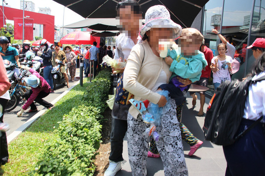 Hàng ngàn người đội nắng giành đồ chơi, thức ăn nhanh miễn phí tại một cửa hàng ở TP HCM Ảnh: LÊ PHONG