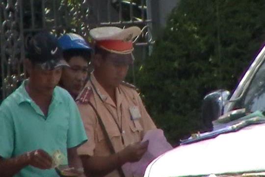 Trong khi CSGT kiểm tra giấy tờ, tài xế phải móc ví. Ảnh cắt từ clip do phóng viên Báo Người Lao Động ghi được