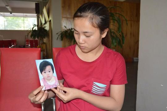 Chị Bùi Thị Thúy Lê bên di ảnh của bé Trần Hoàng Kim Anh