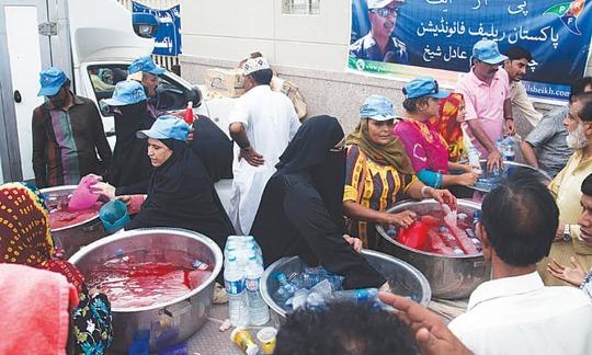 Các tình nguyện viên phát nước cho những người say nắng ở TP Karachi. Ảnh: AP