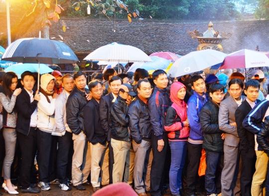 Dù trời mưa rất to, nhưng người dân vẫn kiên trì xếp hàng dài để xin ấn