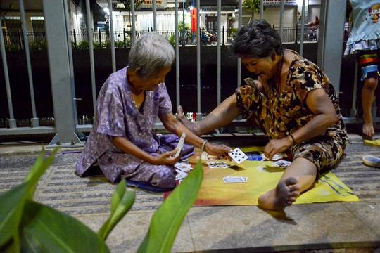 Hai cụ bà vô tư ngồi chơi đánh bài.