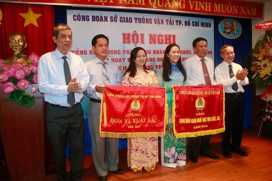 Ông Nguyễn Văn Khải, Phó Chủ tịch Thường trực LĐLĐ TP HCM (bìa trái), tặng cờ thi đua xuất sắc cho Công đoàn Sở Giao thông Vận tải Ảnh: KHÁNH CHI