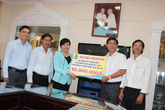 Đại diện LĐLĐ quận 11 (bên phải) trao tiền của CNVC-LĐ quận đóng góp xây Khu Tưởng niệm chiến sĩ Gạc Ma cho LĐLĐ TP HCM