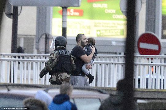 Một con tin ôm đứa bé chạy khỏi cửa hàng. Ảnh: