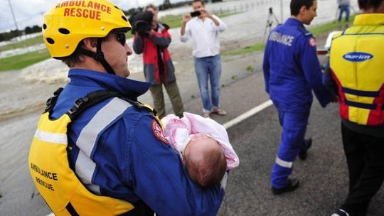 Một em bé được cứu thoát khỏi TP Maitland. Ảnh: Sydney Morning Herald