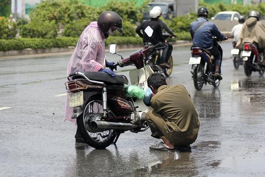 Một người đàn ông sửa bu-gi giữa đường.