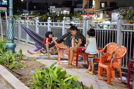 Bất chấp nguy hiểm, nhiều gia đình vẫn cho các em nhỏ ngồi chơi bên bờ kênh.
