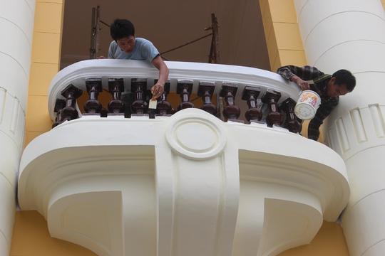 Thợ sơn đang sơn những lớp nhạt hơn đè lên lớp sơn vàng đậm trước ngôi nhà