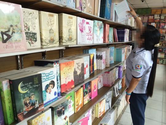 Một nữ sinh trung học tìm sách ngôn tình chất đầy trên kệ ở cửa hàng sách tại TP HCM