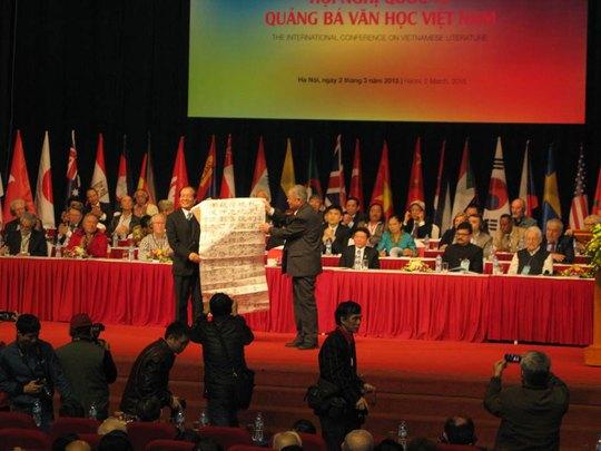 Dịch giả Chúc Ngưỡng Tu (phải, giữa ảnh) tặng nhà thơ Hữu Thỉnh bài thơ của Chủ tịch Hồ Chí Minh do ông chuyển ngữ tại Hội nghị quảng bá văn học Việt Nam ra thế giới lần thứ 3 Ảnh: LÊ NAM