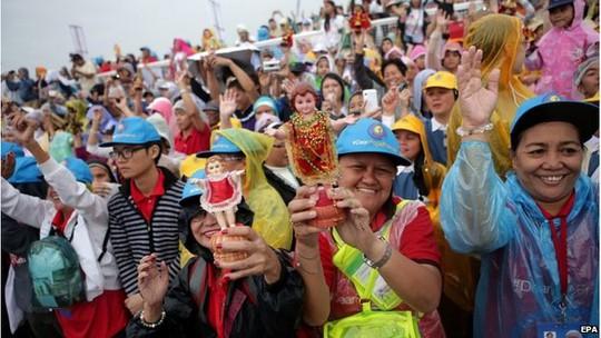 Một số người mặc áo mưa tham dự sự kiện. Ảnh: EPA