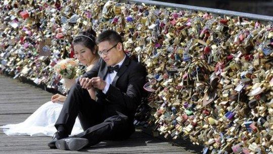 Cặp đôi chụp ảnh cưới trên cầu Pont des Arts ở Pháp. Ảnh: AP